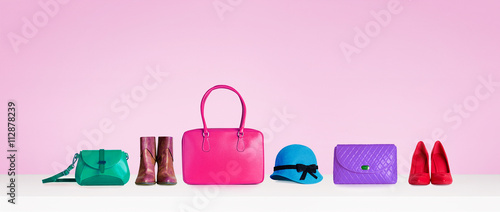 Colorful hand bags,purse,shoes, and hat isolated on pink background. Woman fashion accessories items. Shopping image.  - fototapety na wymiar