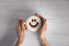 Woman Hands Holding Cup Of Coffee With Creative Pattern On Wooden Table