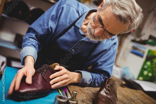 Cobbler examining shoe in workshop
