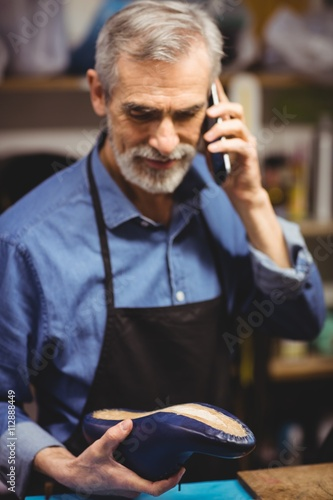 Portrait of cobbler calling and holding a shoe