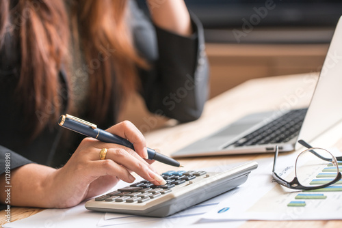 Close up of female accountant or banker making calculations. Sav Canvas Print