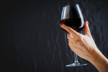 Hand Holding Glass Of Red Wine...