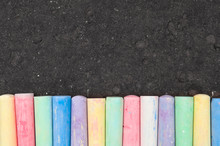 Colorful Pastel Sidewalk Chalk On Dark Asphalt Background.