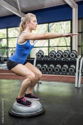 Woman exercising with bosu ball - 112916248