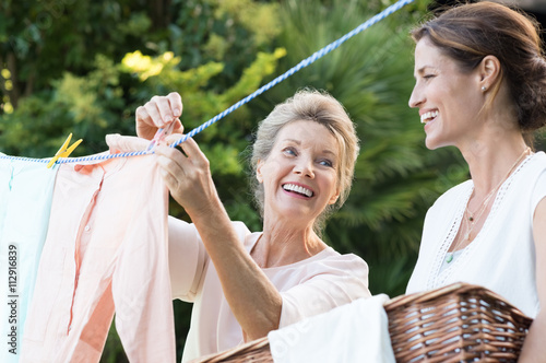 Fotografia, Obraz  Mother daughter doing laundry