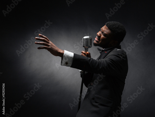 Afro amerian man singing into vintage microphone - 112921436