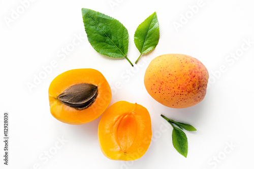 Fresh whole and sliced apricot with leaves. Isolated. White background