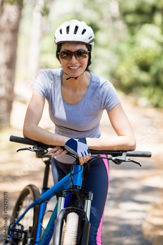 Poster Cycling Woman smiling and posing with her bike