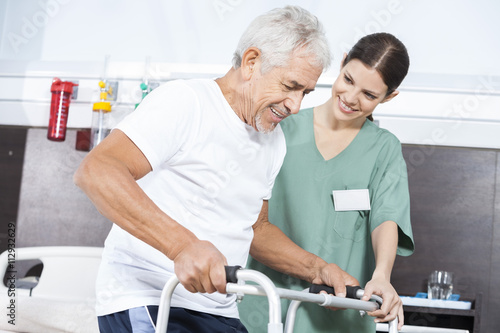 69b0890cd7a Nurse Looking At Patient Using Walker In Rehab Center. By Tyler Olson