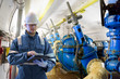Worker using digital tablet to take readings in straining gallery in hydroelectric power station