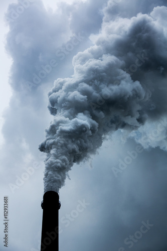 China, Chongqing, Steam and smoke billows from smokestacks at massive coal-fired power plants on cloudy autumn afternoon