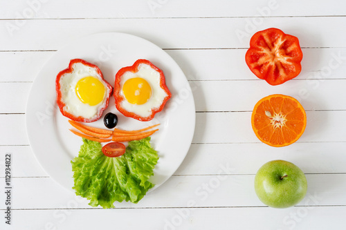 Breakfast for kids. Colorful funny face on plate made with fresh healthy food. White wooden background