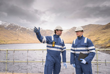 Workers On Dam With Water At Hydroelectric Power Station