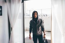 Man In Doorway Wearing Hooded Top Carrying Holdall