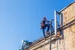Industrial climber climbs up the stairs to the roof. worker in harnesses for working at heights climbs onto the roof. copy space for your text
