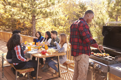 Photo  Man barbecues for friends at a table, on a deck in a forest