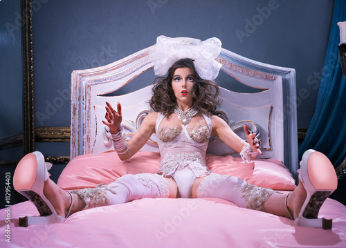 Photographie  Girl as a doll, sitting on the bed in shoes