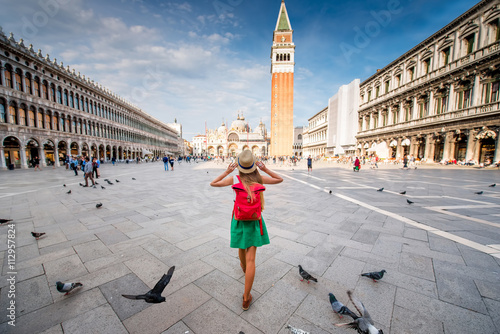Foto op Plexiglas Venetie Young female traveler with hat and backpack standing on San Marco square with tower and basilica on the background in Venice. Back view with copy space