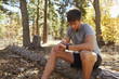 Male runner in a forest sits and checks his smartwatch
