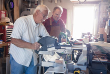 Senior Men Sawing Woodblock In Carpentry Workshop