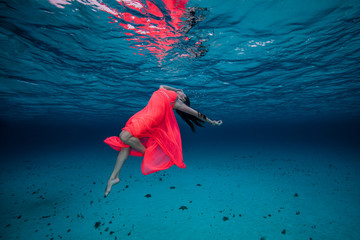 Woman underwater in red dress