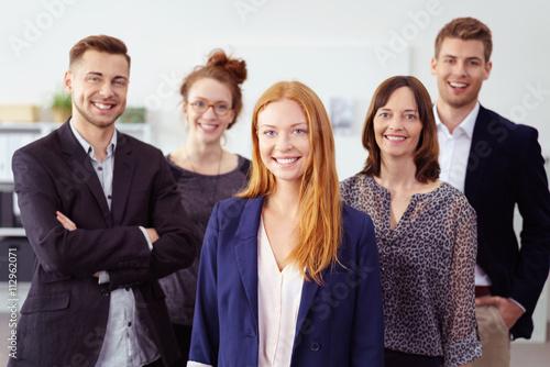 Erfolgreiche junge frau im büro mit kollegen im hintergrund Fototapete