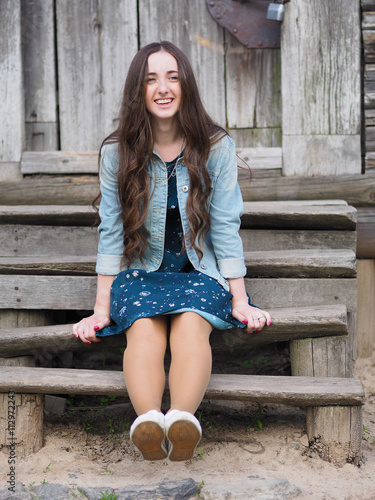 Beautiful Young Woman Sitting On Old Wooden Stairs In Front