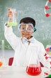 Portrait of schoolboy doing a chemical experiment in laboratory at school
