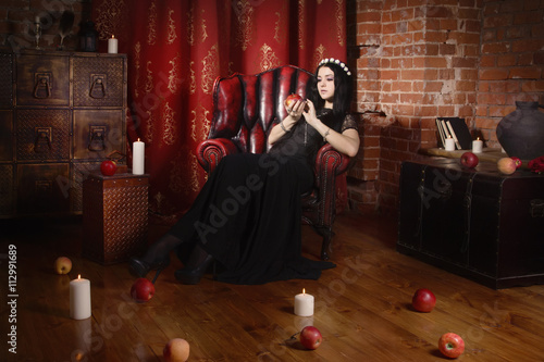 Fotografie, Obraz  Beautiful witch in a black in the dark gothic interior