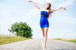 exciting flying like bird: portrait of beautiful brunette young woman having fun jumping high on the road on blue sky outdoors copy space background