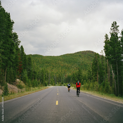 Rear view of two people cycling on a road, Rocky Mountain National Park, Colorad Poster