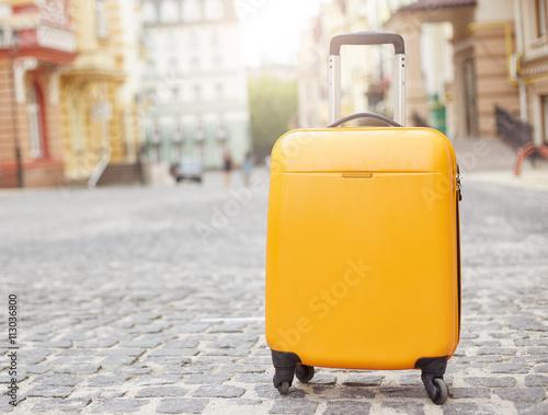 Orange suitcase on the road in city Fototapeta