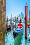 Venice touristic attraction Italy. / View at gondola dock station and church Santa Maria di Salute in background, unique touristic city Venice, Italy.
