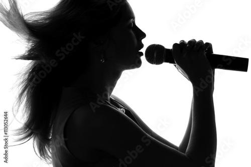 Plakat sylwetka kobiety śpiewa z mikrofonem w ręce