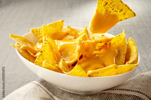 Fotografía  Chip pulled out of bowl of cheese covered nachos