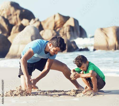 happy family on beach playing, father with son walking sea coast