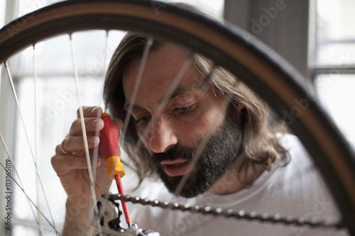 Mid adult man repairing bicycle at home
