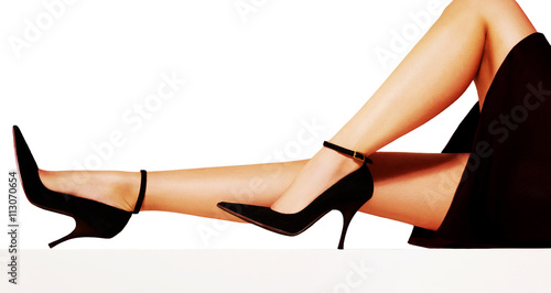 Valokuvatapetti Beautiful woman legs with black skirt and high heels with ankle belt shoes isolated on white background