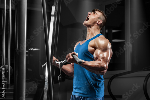 plakat Muscular man working out in gym doing exercises at biceps, strong male