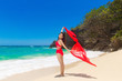 Young beautiful Asian girl with red cloth on the beach of a trop