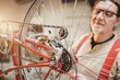 Portrait of a bike mechanic positioned behind a bike wheel