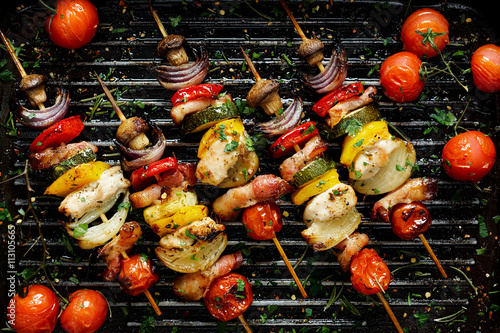 Fototapeta Grilled vegetable and meat skewers in a herb marinade on a grill pan, top view