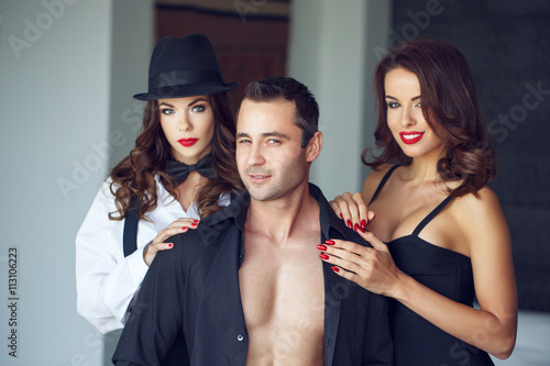 Pinturas sobre lienzo  Sexy macho man winking with two hot lovers