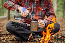 Man Traveler Pours Water From A Bottle Into A Metal Mug.