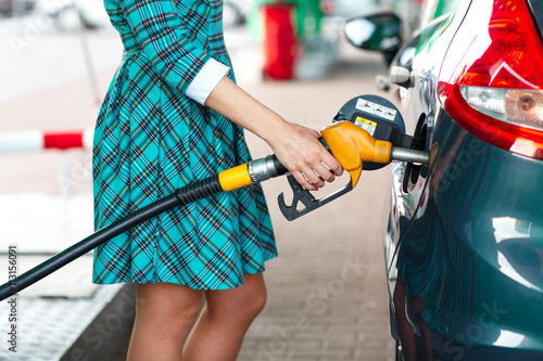 Fotografie, Obraz  Woman fills petrol into the car at a gas station