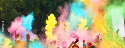 Foto  Crowd of people throwing colored powder