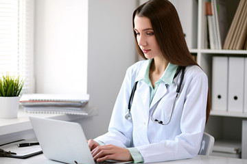 Female doctor brunette sitting  at the table near the window in hospital and typing at laptop computer