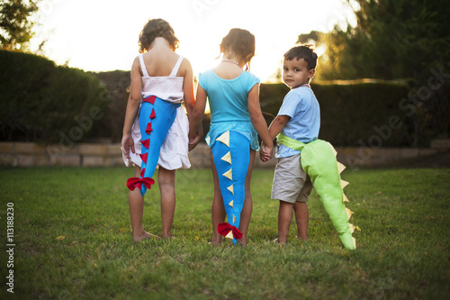 Children (2-3, 4-5, 6-7) wearing dinosaur tail costumes in backyard Poster
