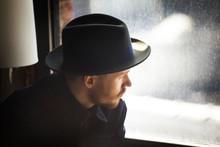 Man In Fedora Looking Through ...