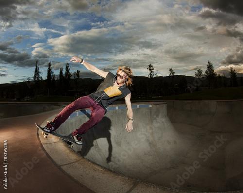 Skater doing trick on rim of bowl Poster